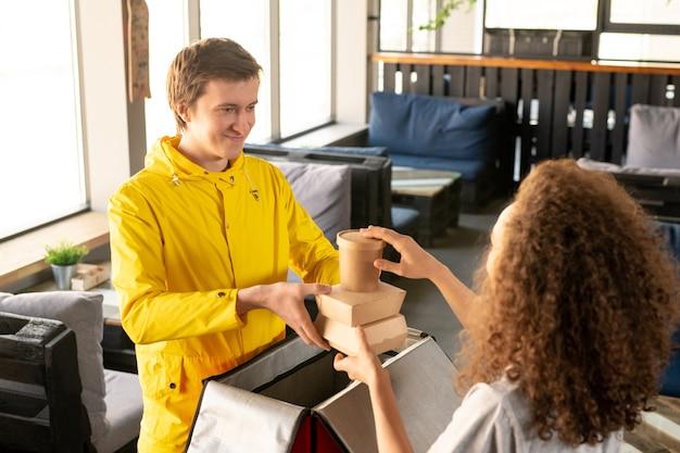 Улыбающийся молодой курьер в желтой куртке упаковывает коробки с едой в термосумку с официанткой в пустом кафе во время эпидемии коронавируса
