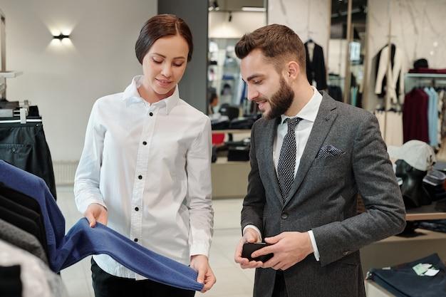 Улыбающийся молодой клиент-консультант показывает свитер во время разговора с бизнесменом в магазине мужской одежды