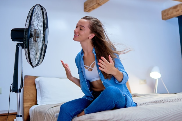 Smiling young cute woman sitting on bed in the bedroom in sunny hot summer day and enjoying of fresh air in the front of electric working fan