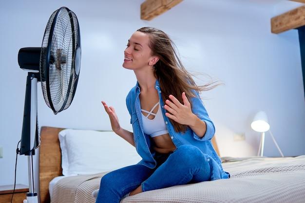 晴れた暑い夏の日に寝室のベッドに座って、扇風機の前で新鮮な空気を楽しんでいる若いかわいい女性の笑顔