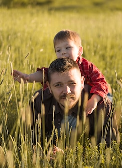 Smiling young dad and son hug relaxing at meadow. happy father and little son rest on the field of feather-grass