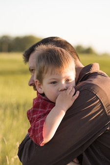 Smiling young dad and son hug relaxing at meadow.