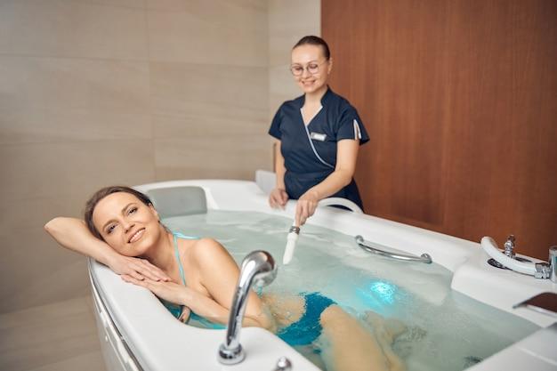 여성 환자의 압력 하에서 물 분사를 지시하는 젊은 검은 머리 치료사 미소