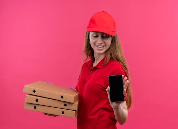 Улыбающаяся молодая доставщица держит пакеты и мобильный телефон и смотрит на мобильный телефон на изолированном розовом пространстве