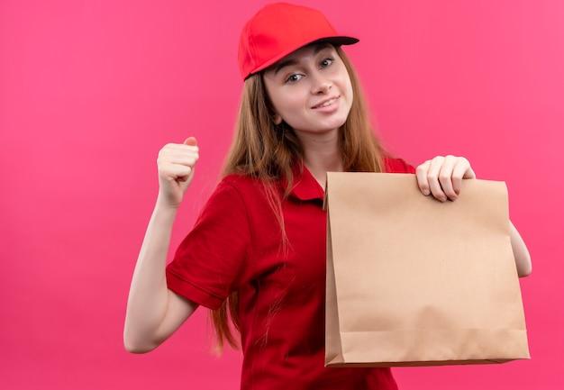 Sorridente giovane ragazza di consegna in uniforme rossa che tiene il sacchetto di carta con il pugno chiuso sulla parete rosa isolata