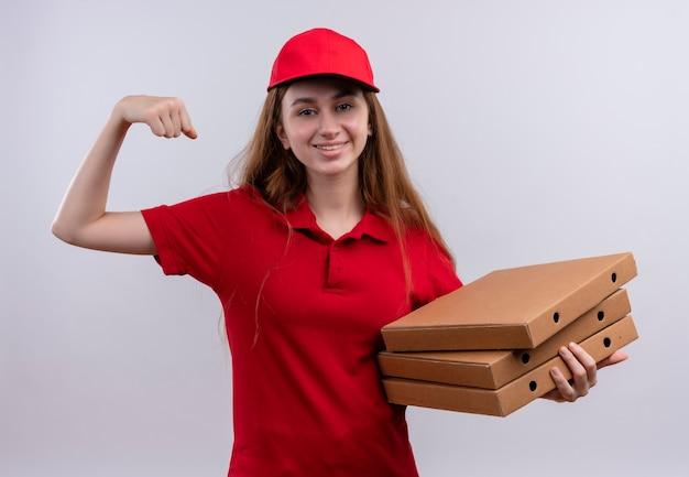 Sorridente giovane ragazza di consegna in uniforme rossa che tiene i pacchetti di pizza facendo un forte gesto sulla parete bianca isolata