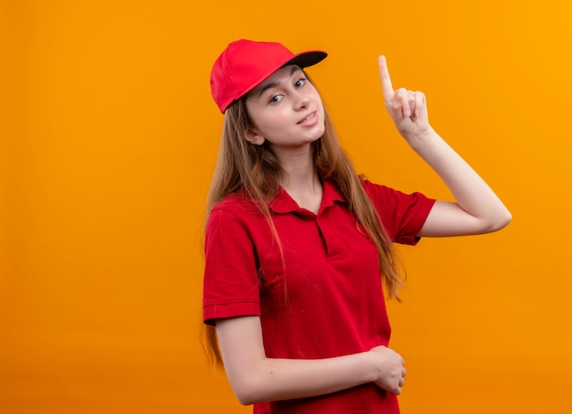 Sorridente giovane ragazza di consegna in uniforme rossa rivolta verso l'alto e mettendo la mano sulla pancia sulla parete arancione isolata con lo spazio della copia