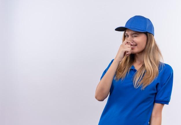 Улыбающаяся молодая доставщица в синей форме и кепке с закрытым носом изолирована на белой стене с копией пространства