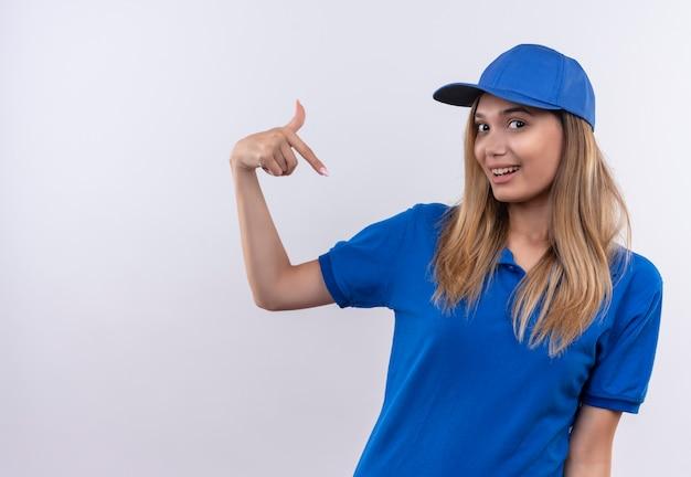 파란색 유니폼과 모자를 입고 웃는 젊은 배달 소녀 자신을 복사 공간이 흰 벽에 고립 된 포인트