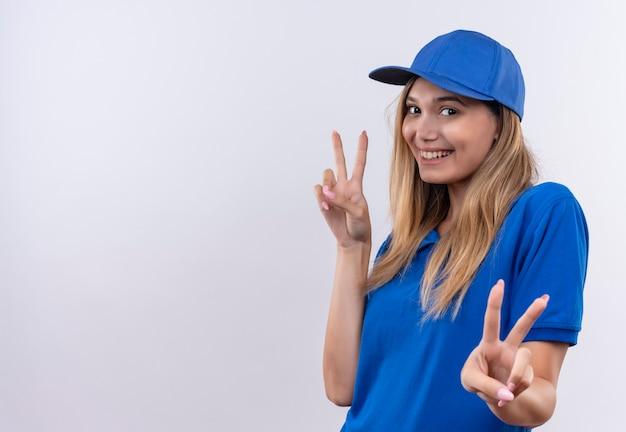 파란색 유니폼과 모자 복사 공간 흰 벽에 고립 된 평화 제스처를 보여주는 젊은 배달 소녀 미소