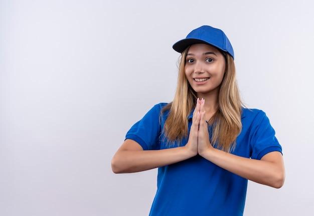 파란색 유니폼과 모자 복사 공간 흰 벽에 고립 된기도 제스처를 보여주는 젊은 배달 소녀 미소
