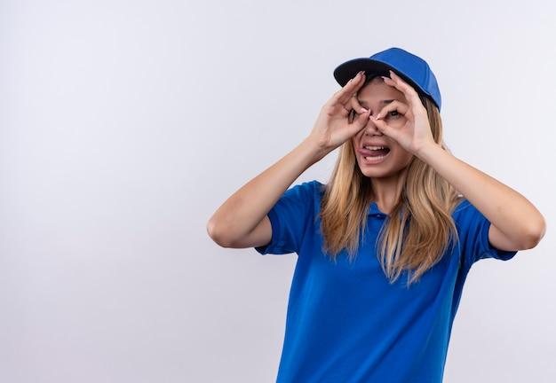 파란색 유니폼과 혀를 보여주는 모자를 쓰고 흰색에 고립 된 제스처를 찾고 웃는 젊은 배달 소녀