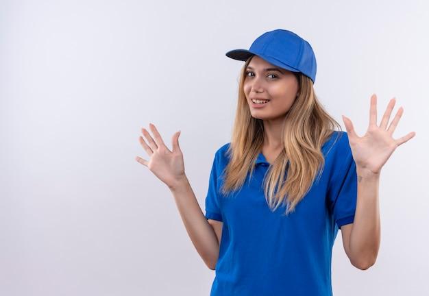 파란색 유니폼과 모자를 입고 웃는 젊은 배달 소녀 복사 공간이 흰 벽에 고립 된 손을 확산