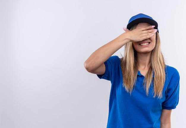 La giovane ragazza sorridente di consegna che porta l'uniforme blu e la protezione ha coperto gli occhi con la mano isolata sulla parete bianca con lo spazio della copia