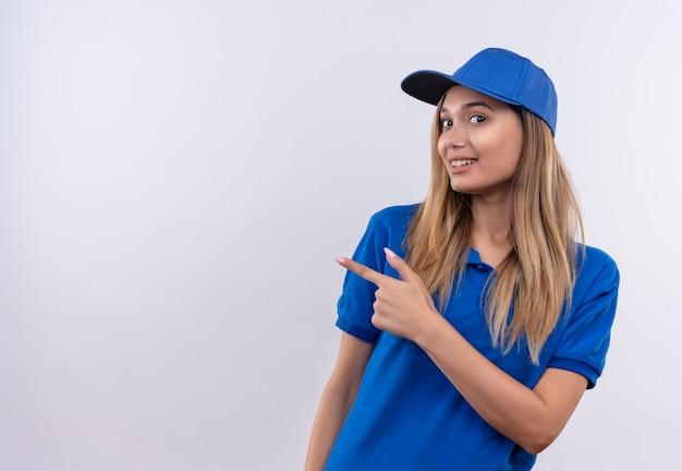 La giovane ragazza sorridente di consegna che porta l'uniforme blu e le punte del cappuccio al lato isolato sulla parete bianca con lo spazio della copia