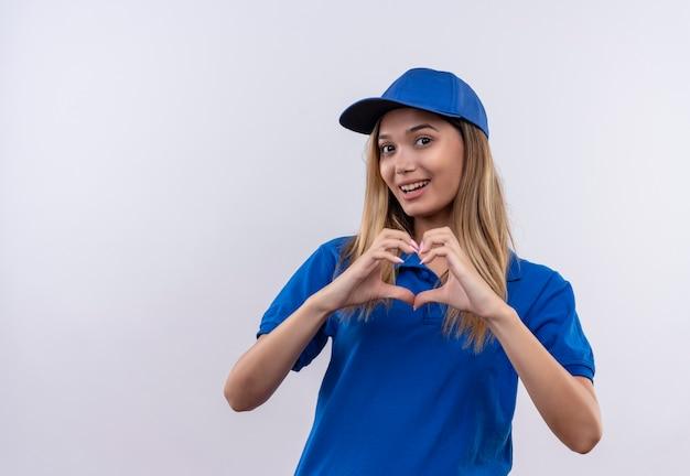 Giovane ragazza sorridente di consegna che indossa l'uniforme blu e cappuccio che mostra il gesto del cuore isolato sulla parete bianca con lo spazio della copia