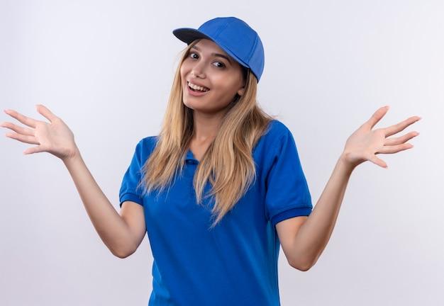 La giovane ragazza sorridente di consegna che porta l'uniforme e il cappuccio blu diffonde le mani isolate sulla parete bianca con lo spazio della copia