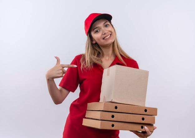 Улыбающаяся молодая доставщица в красной форме и кепке держит и указывает на множество коробок, изолированных на белом