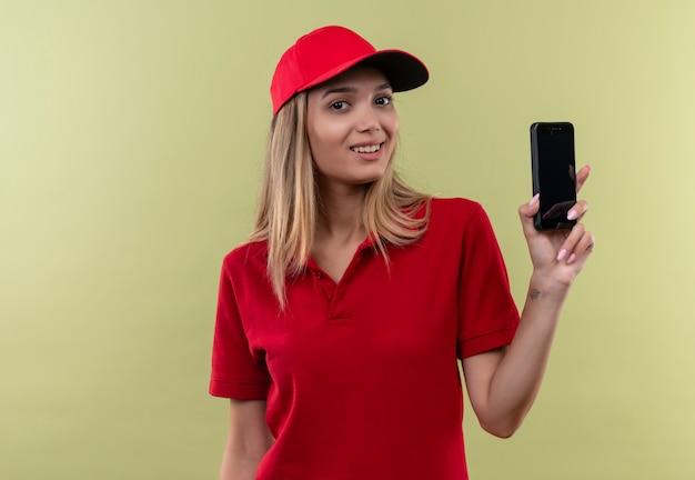 빨간 유니폼과 모자를 쓰고 전화를 들고 웃는 젊은 배달 소녀 격리 된 녹색 벽
