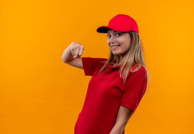 빨간 유니폼과 모자 오렌지 벽에 고립 된 주먹을 보여주는 젊은 배달 소녀 미소