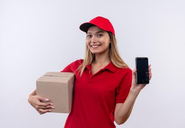 Sorridente giovane ragazza di consegna che indossa l'uniforme rossa e cappello tenendo la scatola e telefono isolato su bianco