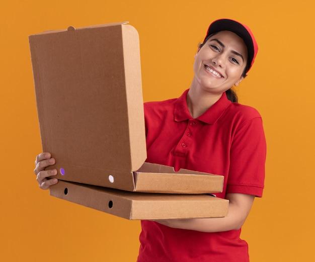 Улыбающаяся молодая доставщица в униформе и кепке держит и открывает коробку для пиццы, изолированную на оранжевой стене