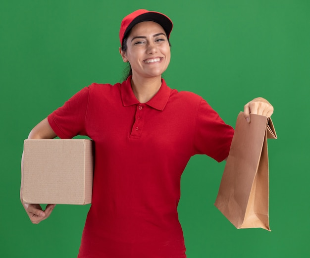 Улыбающаяся молодая доставщица в униформе и кепке держит коробку с бумажным пакетом продуктов, изолированным на зеленой стене
