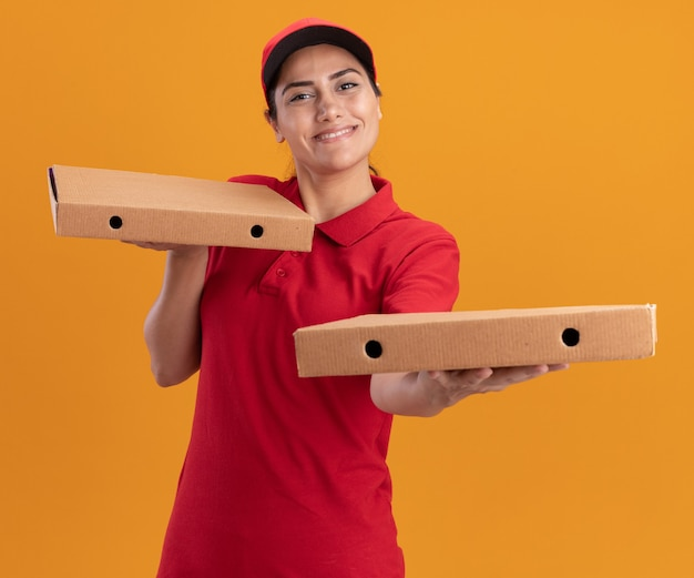 오렌지 벽에 고립 된 앞에 피자 상자를 들고 유니폼과 모자를 입고 웃는 젊은 배달 소녀