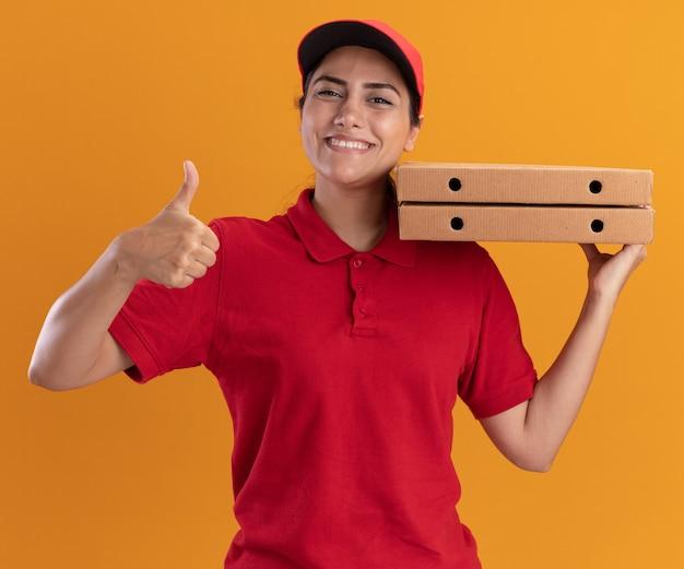 オレンジ色の壁に分離された親指を示す肩にピザの箱を保持している制服と帽子を身に着けている笑顔の若い配達の女の子