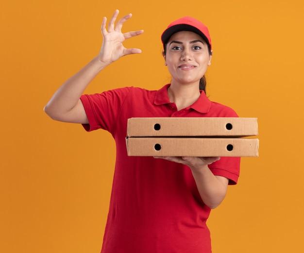 오렌지 벽에 고립 된 크기를 보여주는 피자 상자를 들고 유니폼과 모자를 입고 웃는 젊은 배달 소녀