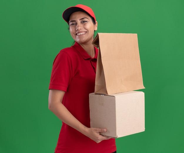 Sorridente giovane ragazza di consegna indossando l'uniforme e la scatola di contenimento del cappuccio con il pacchetto di cibo di carta isolato sulla parete verde