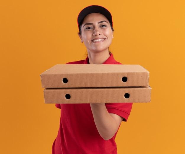 Sorridente giovane ragazza delle consegne indossando l'uniforme e berretto tenendo fuori le scatole per pizza isolate sulla parete arancione