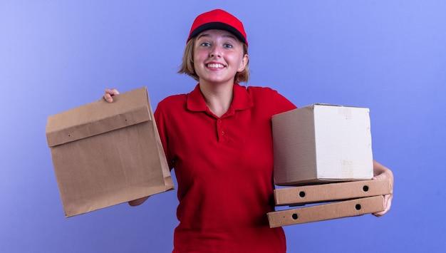Sorridente giovane ragazza delle consegne che indossa l'uniforme e il cappuccio che tiene il sacchetto di carta per alimenti con scatole per pizza isolate sulla parete blu
