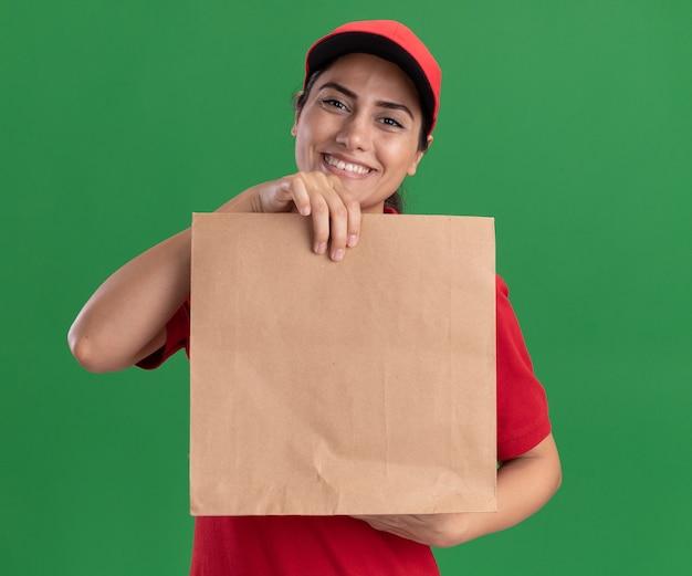 Sorridente giovane ragazza delle consegne che indossa l'uniforme e il berretto che tiene il pacchetto alimentare di carta isolato sul muro verde