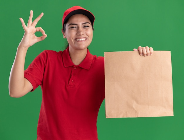 Sorridente giovane ragazza di consegna che indossa l'uniforme e cappuccio che tiene il pacchetto di cibo di carta che mostra gesto giusto isolato sulla parete verde