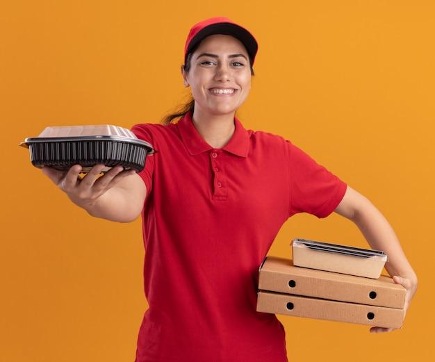 Sorridente giovane ragazza di consegna che indossa l'uniforme e cappuccio che tiene le scatole per pizza e porgendo contenitori per alimenti nella parte anteriore isolata sulla parete arancione