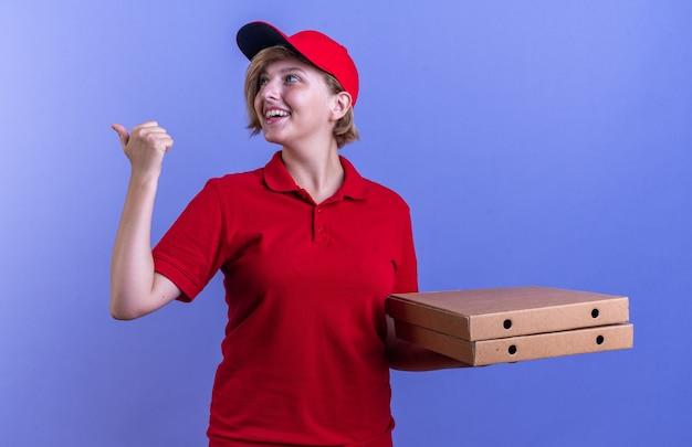 Sorridente giovane ragazza delle consegne che indossa l'uniforme e il cappuccio che tiene le scatole per pizza punti dietro isolato sulla parete blu