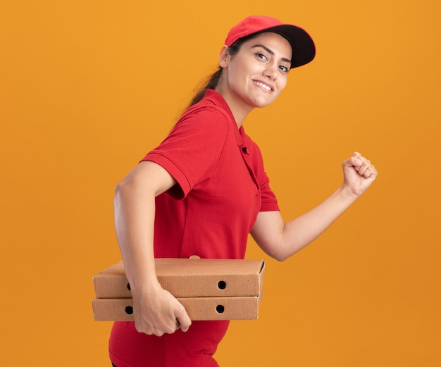 Sorridente giovane ragazza delle consegne che indossa l'uniforme e il berretto che tiene le scatole della pizza che mostra il gesto di corsa isolato sulla parete arancione
