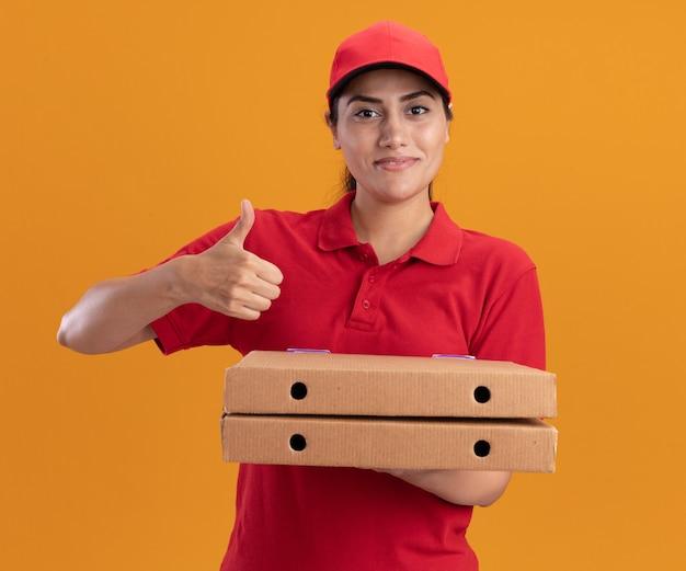 Sorridente giovane ragazza di consegna che indossa l'uniforme e cappuccio che tiene le scatole per pizza che mostrano il pollice in su isolato sulla parete arancione