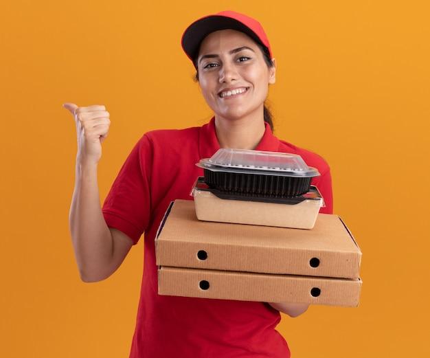 La giovane ragazza sorridente di consegna che indossa l'uniforme e il cappuccio che tiene le scatole per pizza con i contenitori per alimenti indica dietro isolato sulla parete arancione con lo spazio della copia