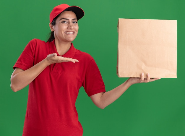 Sorridente giovane ragazza di consegna indossando l'uniforme e la tenuta del cappuccio e punti al pacchetto di cibo di carta isolato sulla parete verde