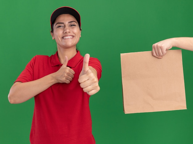 Smiling young delivery girl wearing uniform and cap showing thumb up someone giving money to her isolated on green wall