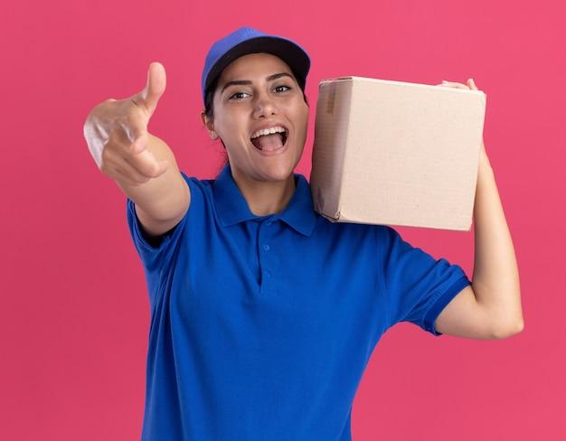 분홍색 벽에 고립 된 제스처를 보여주는 어깨에 상자를 들고 모자와 유니폼을 입고 젊은 배달 소녀 미소