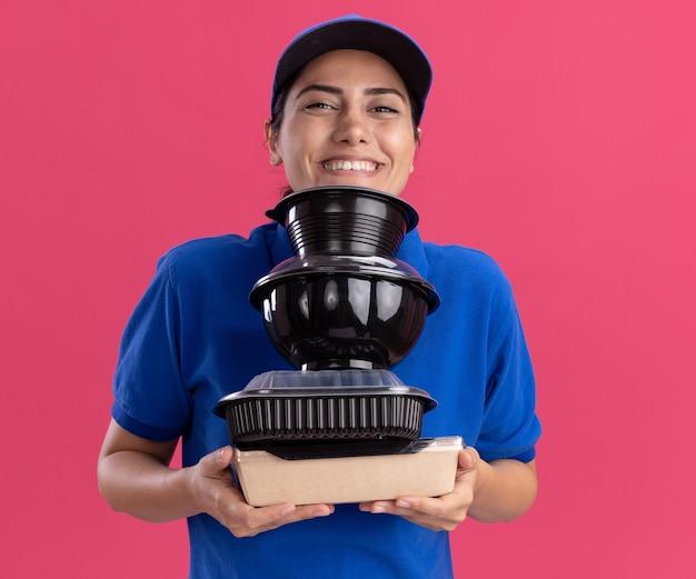 Sorridente giovane ragazza delle consegne che indossa l'uniforme con il cappuccio che tiene i contenitori per alimenti isolati sulla parete rosa