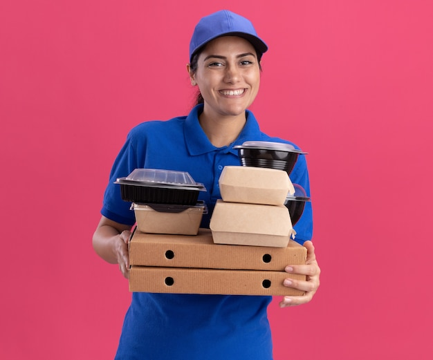 ピンクの壁に分離されたピザの箱に食品の容器を保持しているキャップで制服を着た笑顔の若い配達の女の子