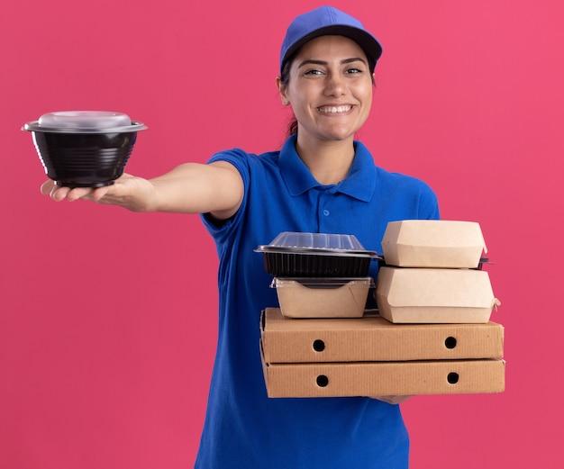 Sorridente giovane ragazza di consegna che indossa l'uniforme con cappuccio che tiene i contenitori per alimenti sulle scatole per pizza tenendo fuori il contenitore per alimenti alla macchina fotografica isolata sulla parete rosa