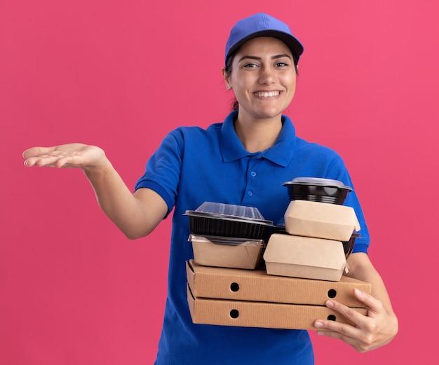 Sorridente giovane ragazza delle consegne che indossa l'uniforme con il cappuccio che tiene i contenitori per alimenti su scatole per pizza punti con la mano a lato isolata sulla parete rosa