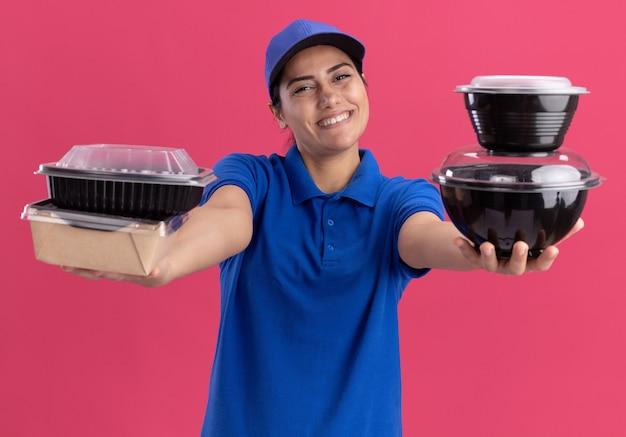 Sorridente giovane ragazza di consegna che indossa l'uniforme con cappuccio che tiene fuori i contenitori per alimenti nella parte anteriore isolata sulla parete rosa