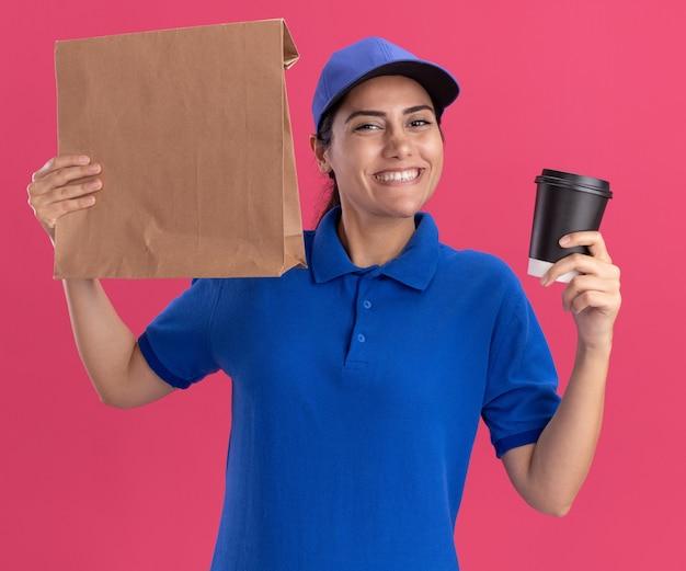 Улыбающаяся молодая доставщица в униформе с кепкой держит бумажный пакет продуктов с чашкой кофе, изолированным на розовой стене