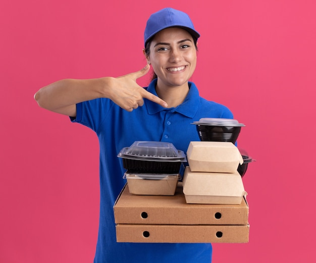 Smiling young delivery girl wearing uniform with cap holding and points at food containers on pizza boxes isolated on pink wall